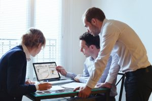 three people around a desk reviewing a tableau dashboard on a laptop